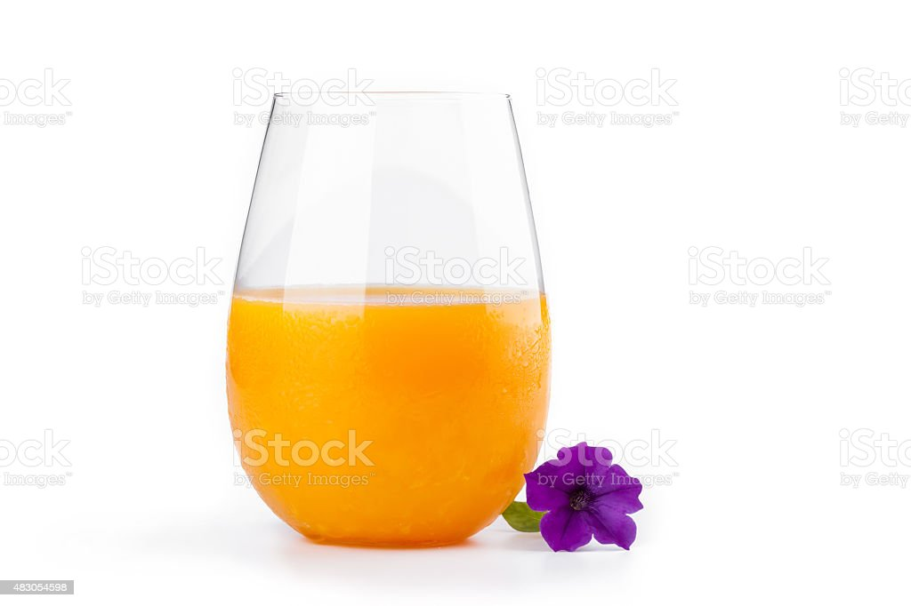 The glass of fresh orange juice and beautiful violet flower. stock photo