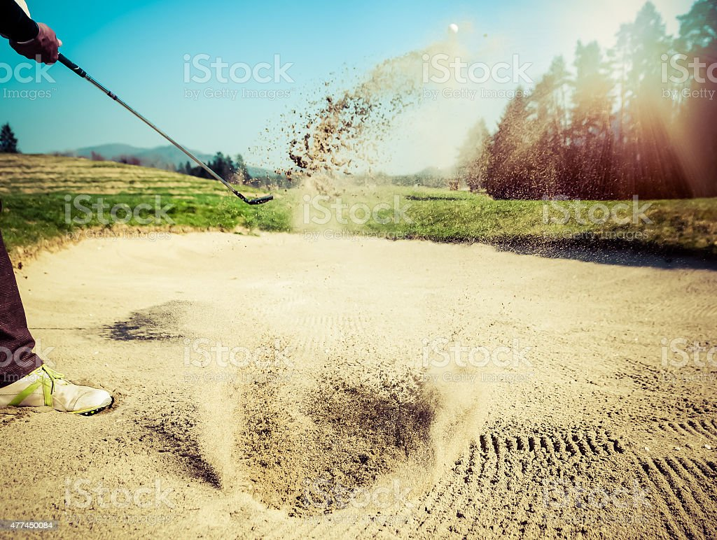 Golfer hitting out of a sand trap. The golf course is on the sand....