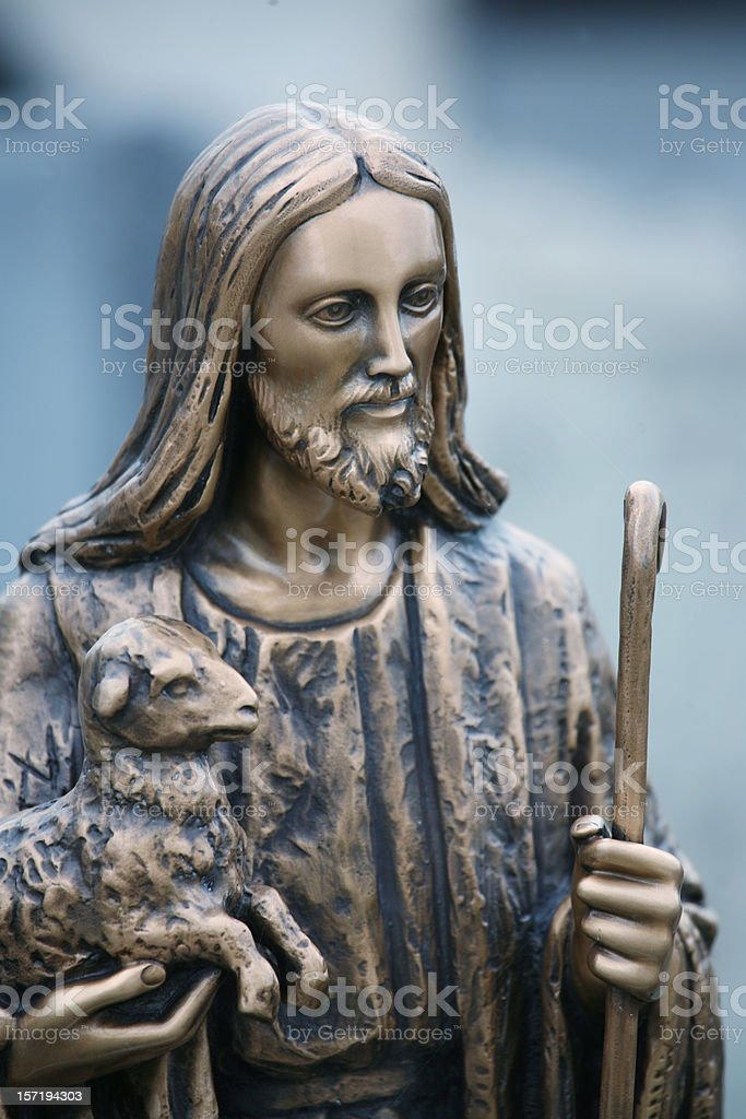 The good shepherd: Golden Jesus statue with lamb on arms royalty-free stock photo
