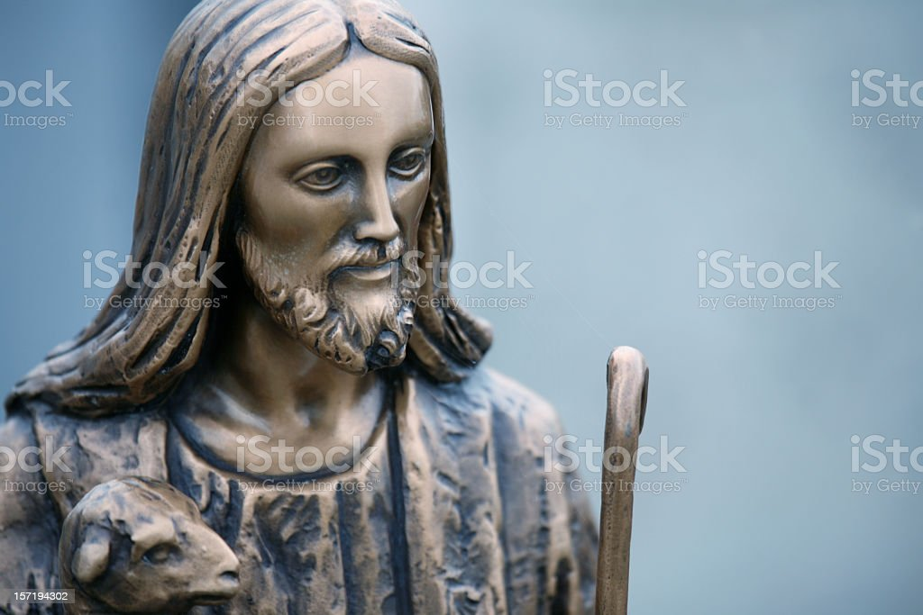 The good shepherd: Jesus statue with lamb stock photo