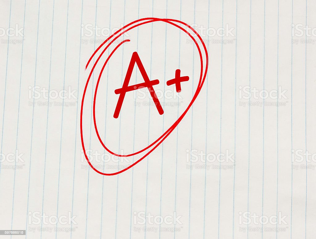 The grade A plus (A+) written in red on notebook paper stock photo