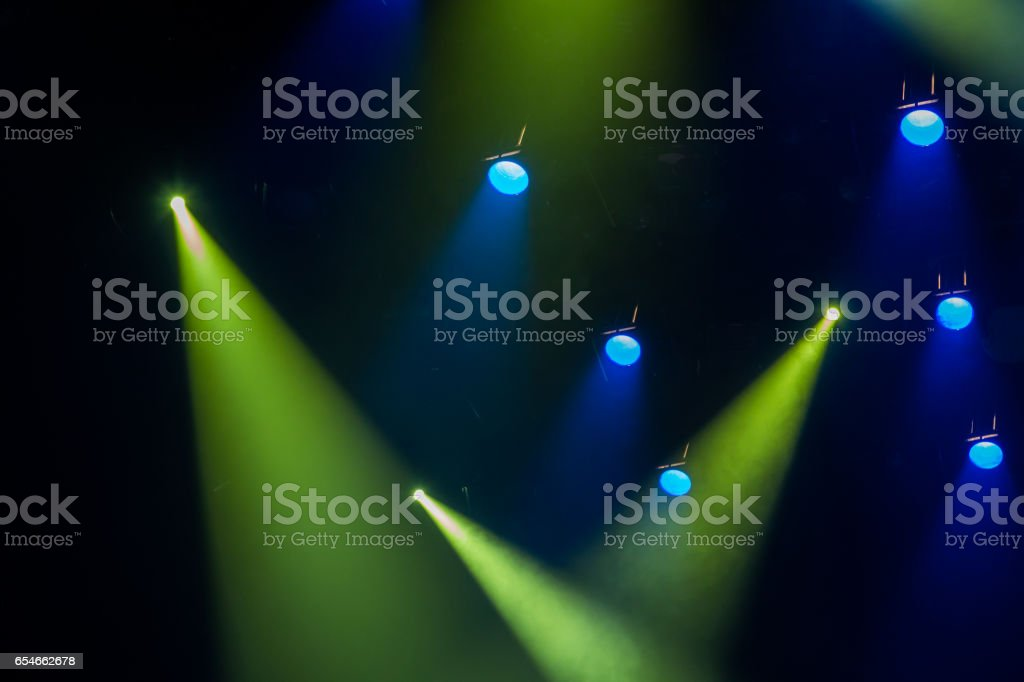 The green-blue light from the spotlights through the smoke in the theatre during the performance. Lighting equipment stock photo