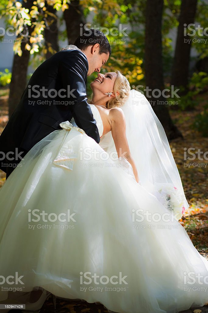 The groom holds bride leaning for support. royalty-free stock photo