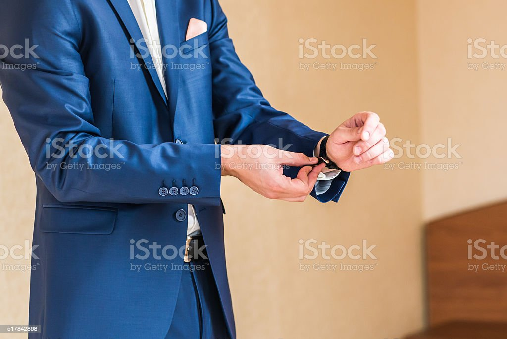 the groom puts on a watch stock photo