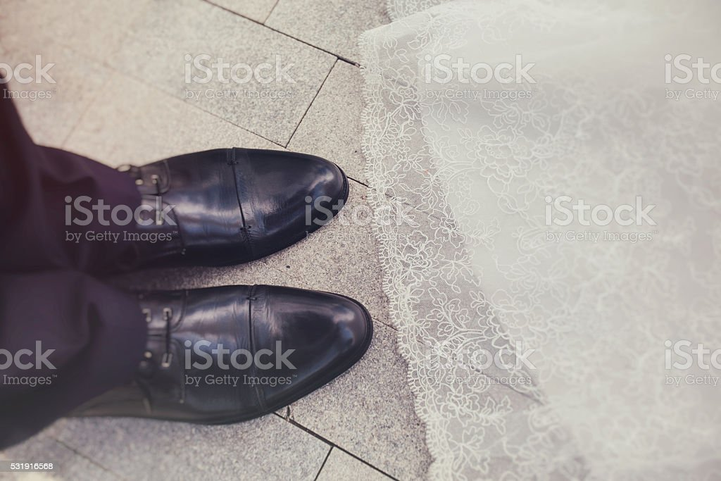 the groom's shoes and hem of the bride stock photo