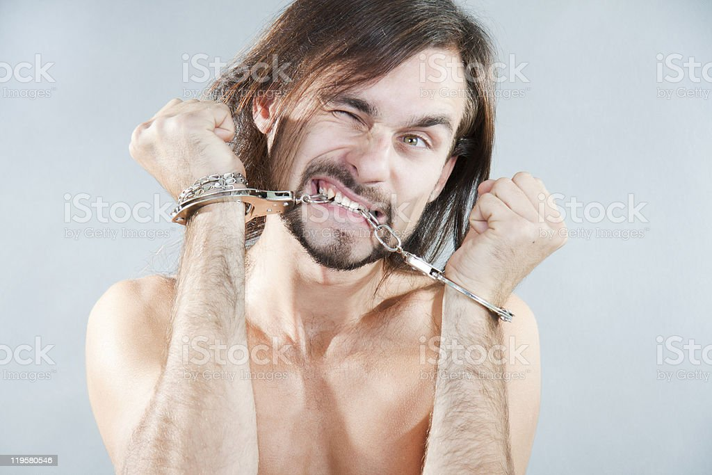 The guy gnaws his handcuffs royalty-free stock photo