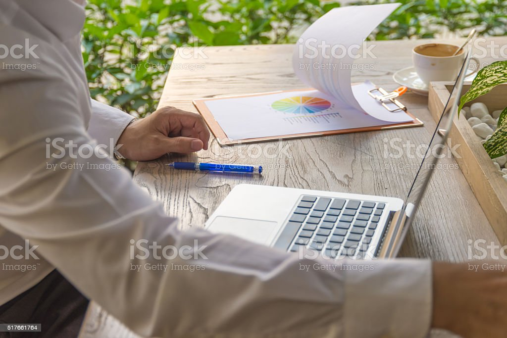 The guy with chart document, pen, laptop and coffee stock photo