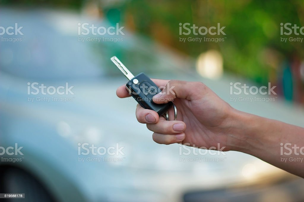 the hand holding the key FOB from the vehicle stock photo