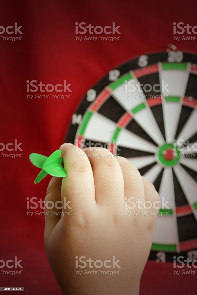 The hand holds a dart for darts. stock photo