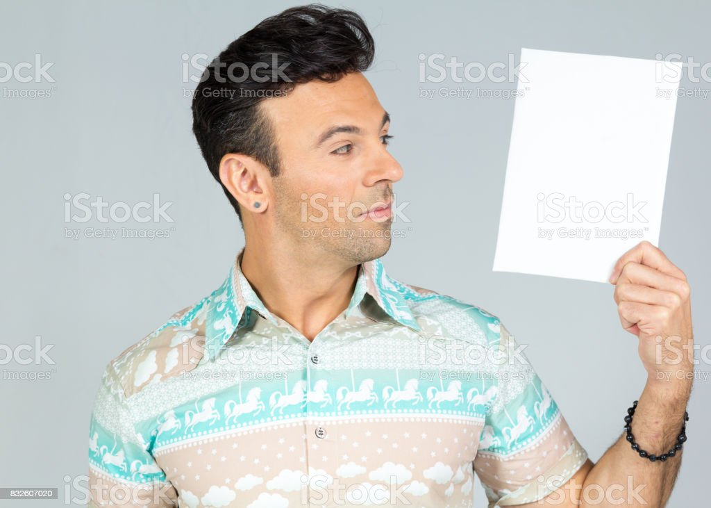 The hand holds a rectangular paper vertically. Space for text. Man looks into empty space. Handsome brazilian male wearing a colorful shirt. Summer, tropical. 30s. Fit and athletic. stock photo