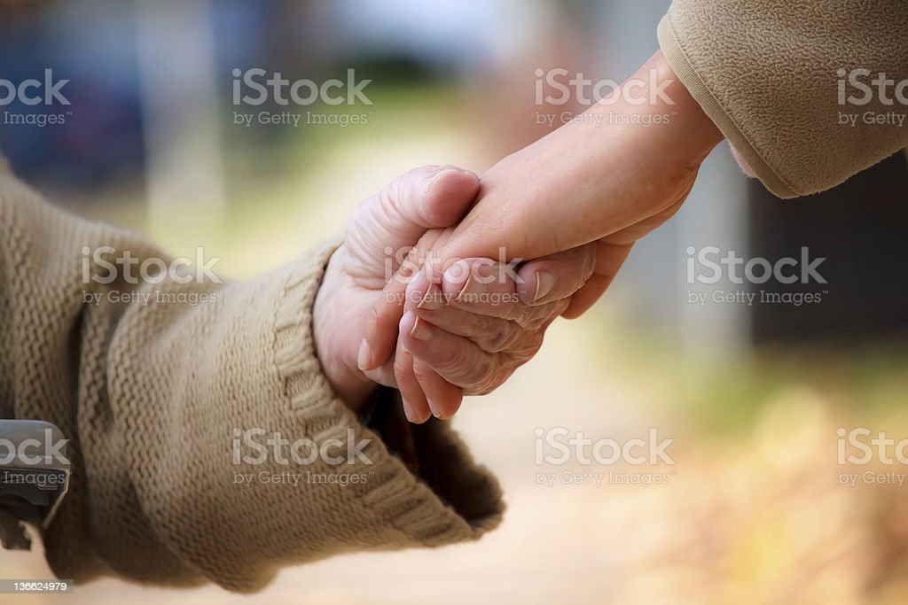 The hand of an elderly person holding the hand of a child royalty-free stock photo