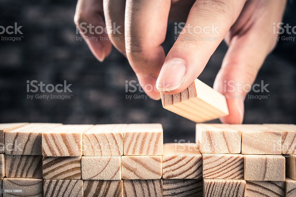 The hand of man has piled up a wooden block stock photo