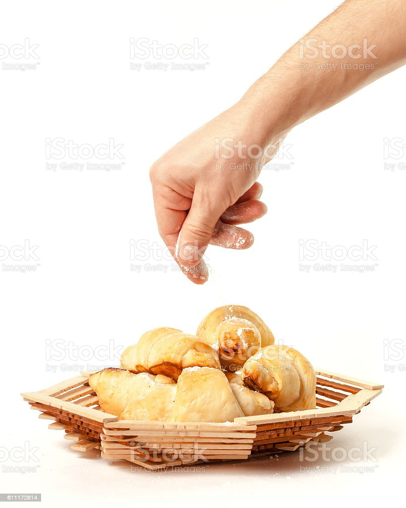 The hand of man sprinkles powdered homemade cakes stock photo