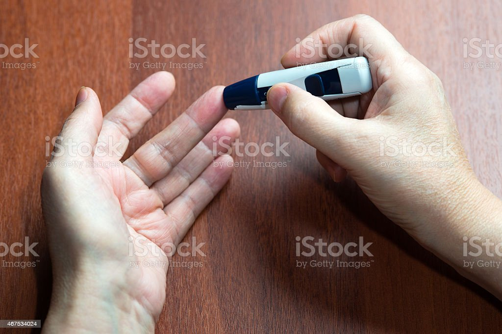 the hand of the elderly woman lies near the device stock photo