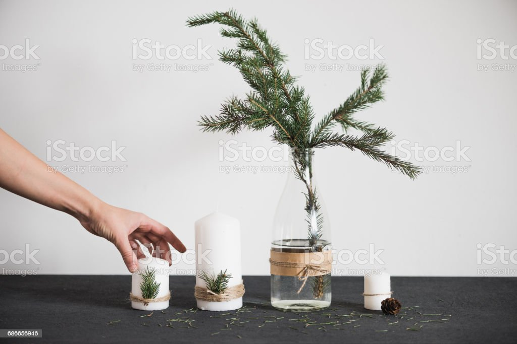 The hand puts a candle on the table. Chritmas decorations on tha table, spruce branch, pine cones stock photo