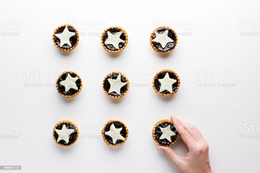 The hand puts star shaped tarts on the table, top view, on white stock photo