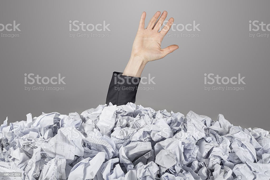 The hand reaches out from big heap of crumpled papers stock photo