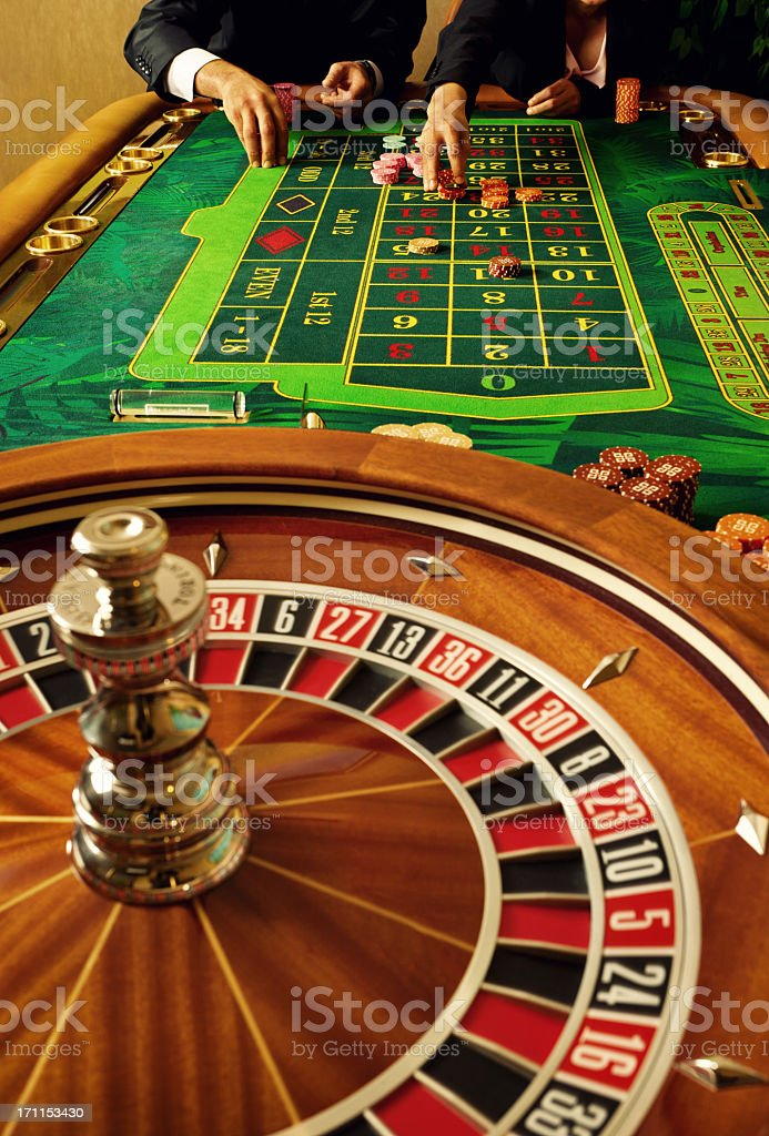 The hands and torsos of two gamblers playing casino roulette stock photo