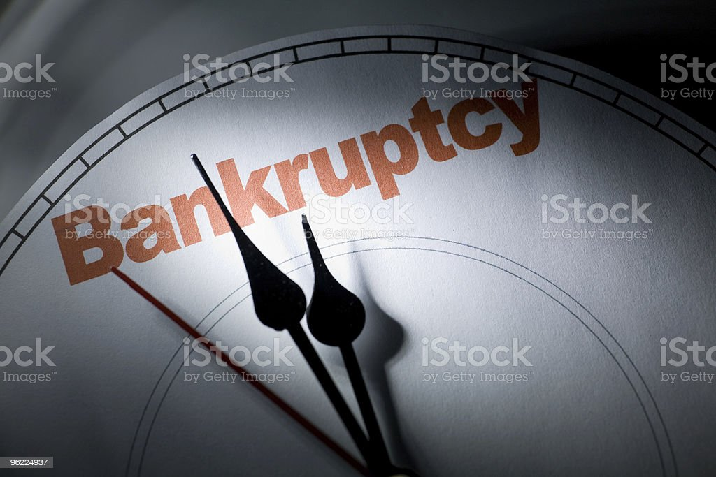 The hands of a retro clock pointing to Bankruptcy stock photo