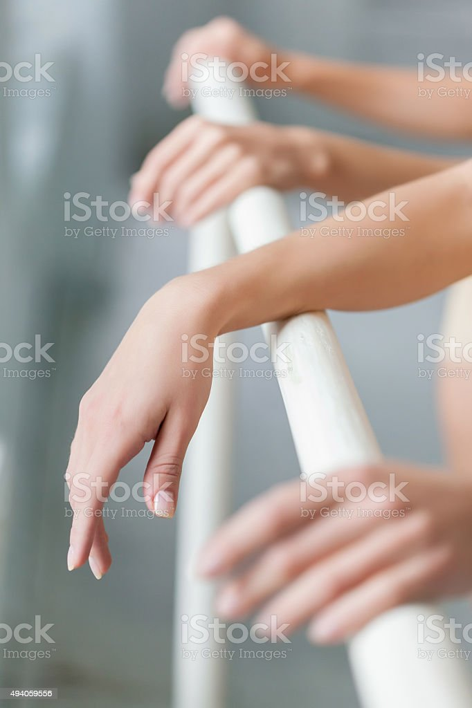 The  hands of two classic ballet dancers at barre stock photo