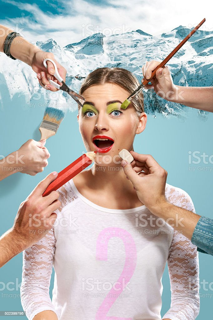 The hands of visagists doing make-up young woman stock photo
