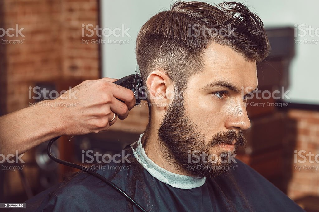 The hands of young barber making haircut to attractive man stock photo