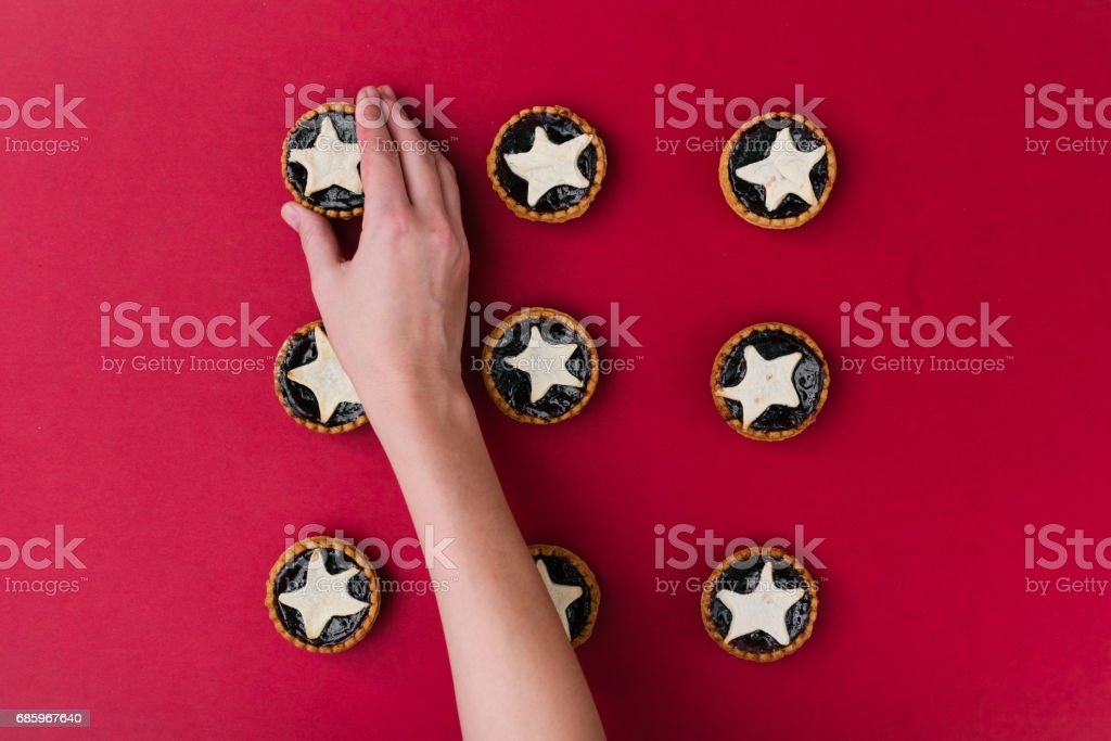 The hands put star shaped tarts on the table, top view stock photo