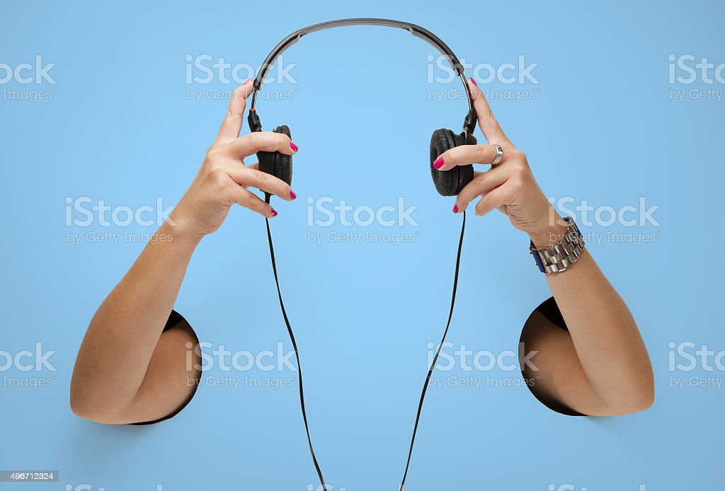 The headphones in a female hands through the holes stock photo