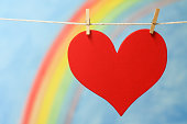 The heart symbol with a rainbow and blue sky background.