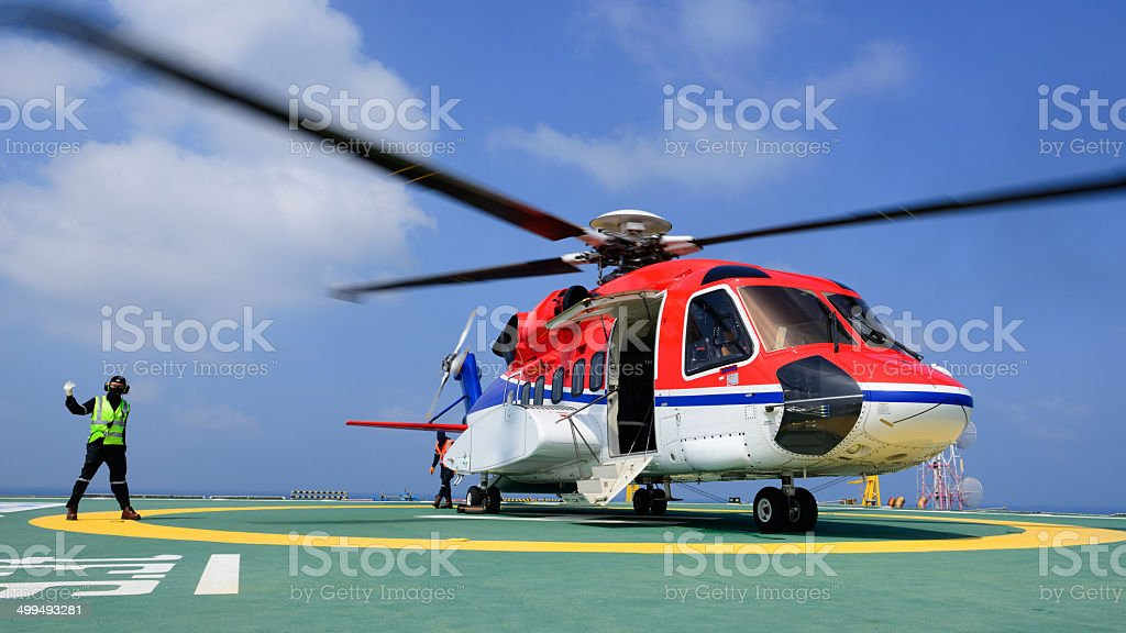 The helicopter landing officer give signal to passenger for embark stock photo