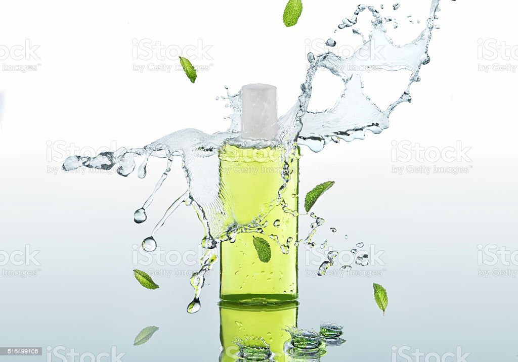 The herbal  moisturizing shampoo stands on the water background stock photo