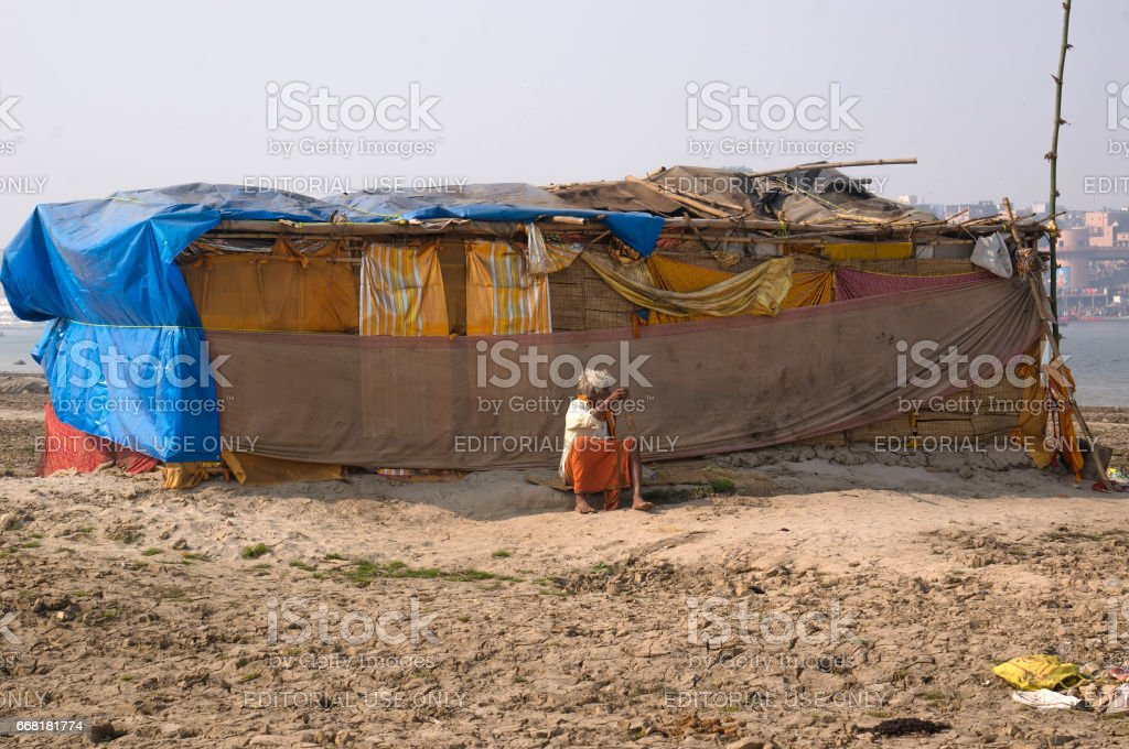 The hermit, a sadhu, sits meditating on the Holy river Ganges stock photo