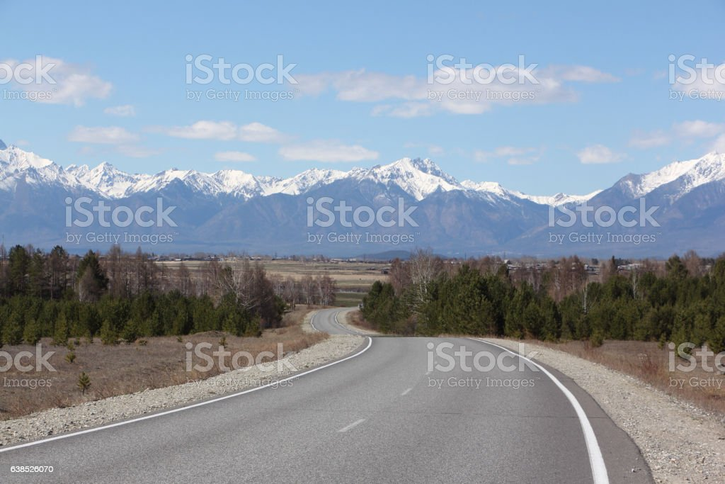 The highway among trees and the Sayan Mountains stock photo