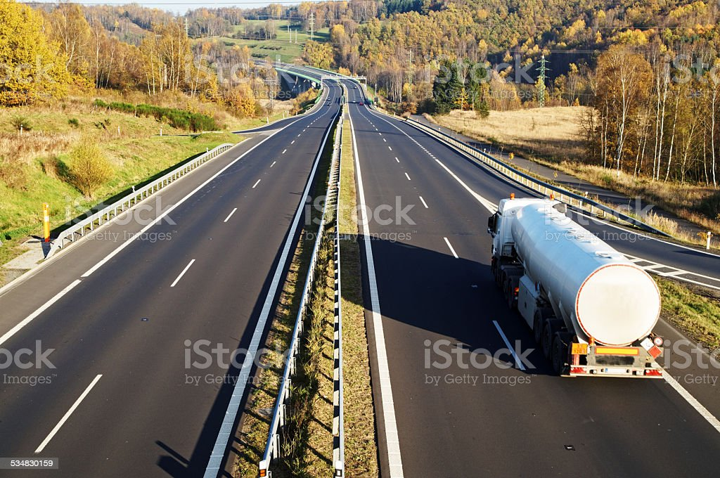 The highway between deciduous trees in autumn colors, white tank stock photo