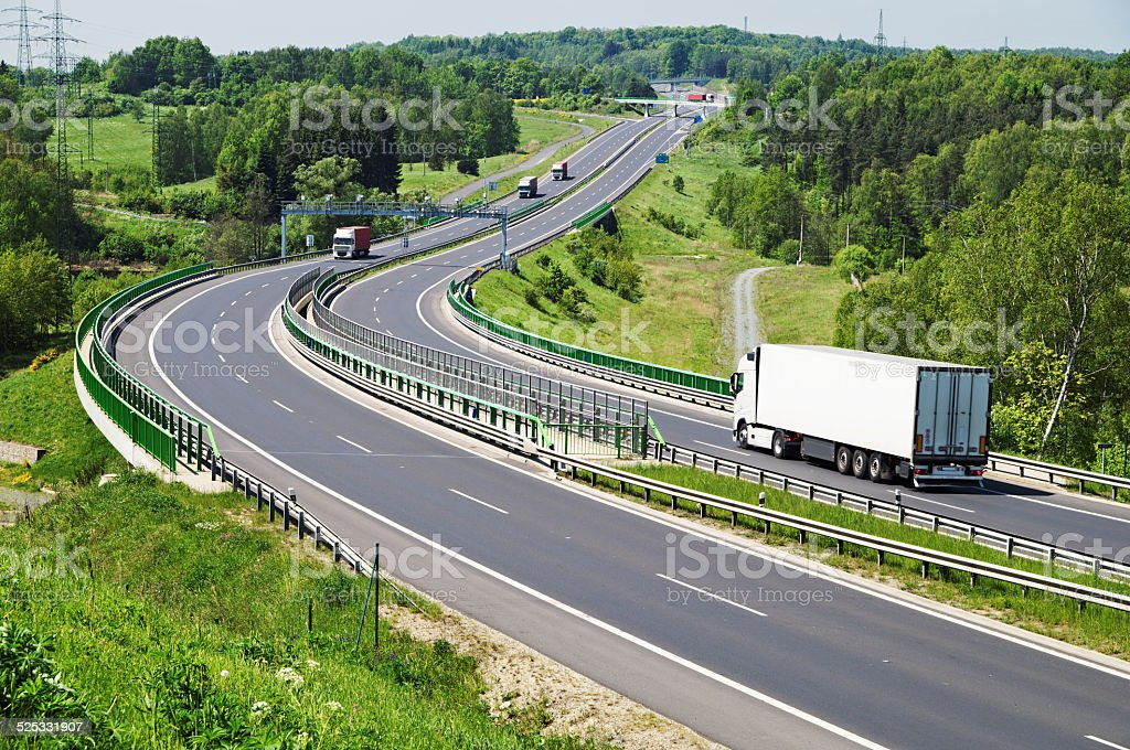 The highway between woods, electronic toll gates, moving trucks stock photo