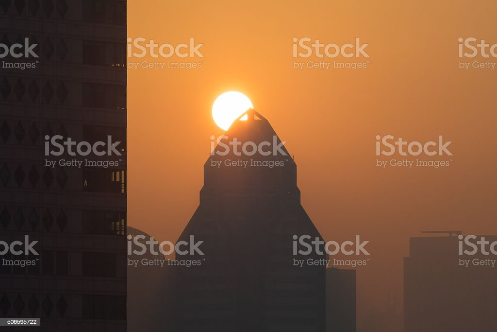 The hope of a new day, rising sun over skyscraper stock photo