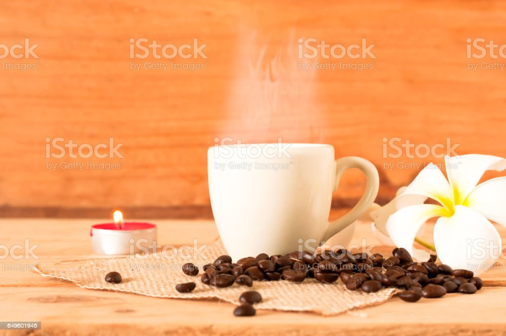 the hot coffee in the white cup on wooden table with coffee seed and red candle stock photo