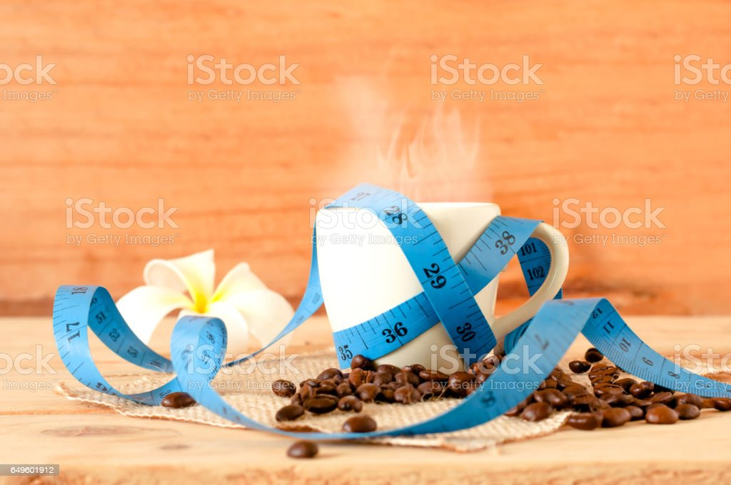 the hot coffee in the white cup with blue measuring tape on wooden table and coffee seed. healthy and diet drink stock photo