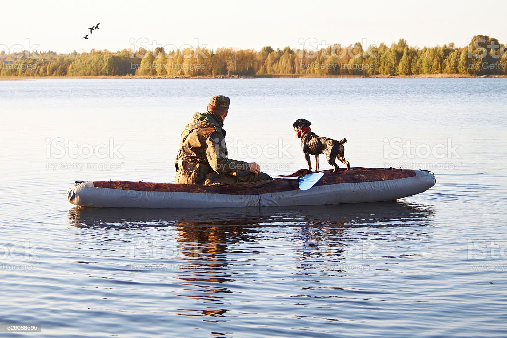 The hunter with a dog in the boat in the middle of the lake stock photo