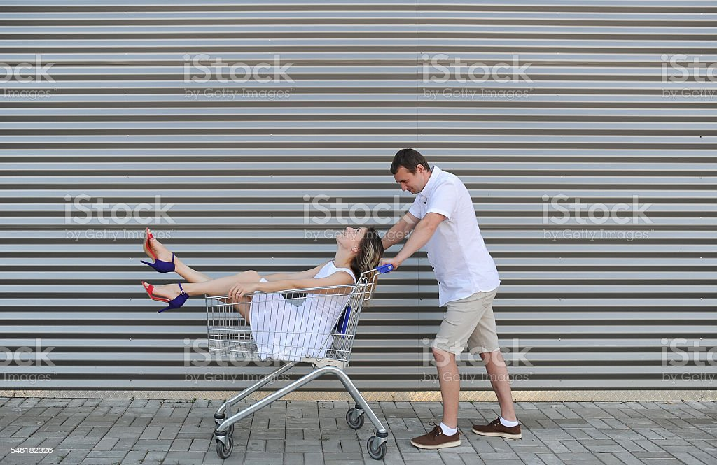 The husband rolls the wife in the cart for foodstuff. stock photo