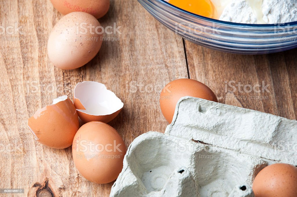 The image of eggs and flour on a wooden table. stock photo