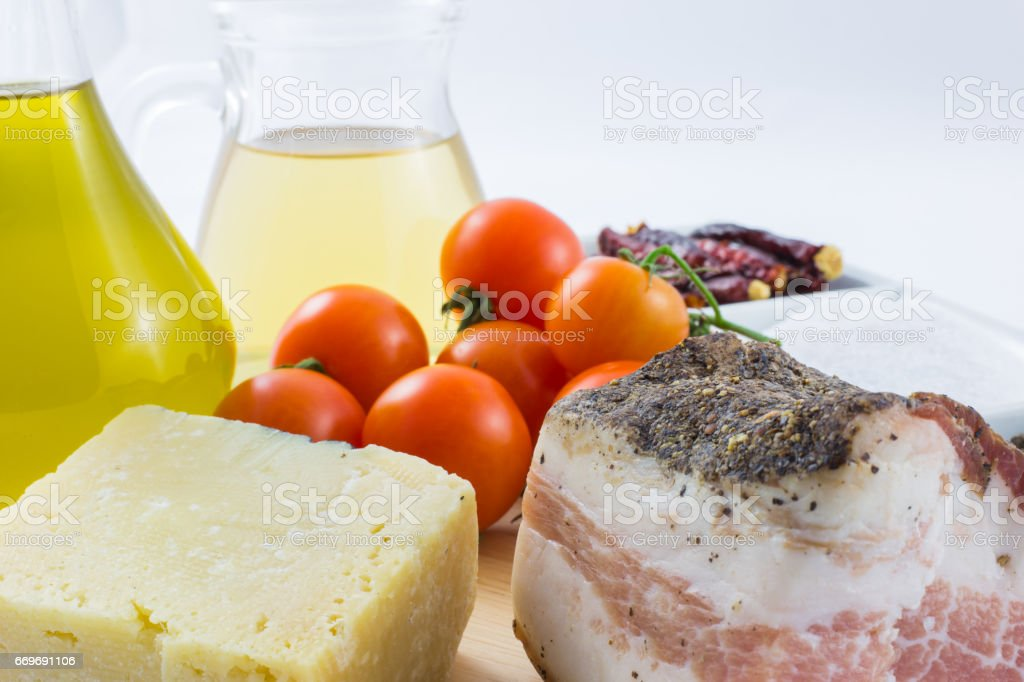 The ingredients for the pasta Amatriciana including bacon, cheese, tomato, pepper and chili. stock photo