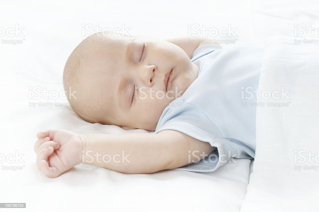 The innocent looking baby in blue is sleeping soundly royalty-free stock photo