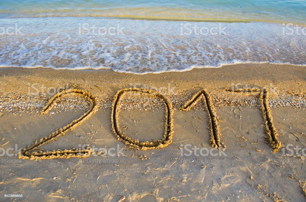 the inscription '2017' on the sand stock photo
