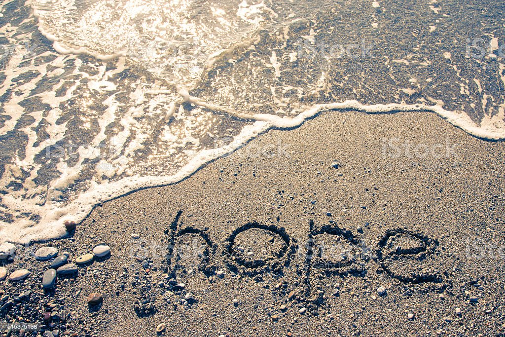 The inscription 'HOPE' on a wet sand seacoast. Toned stock photo