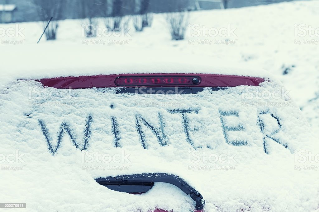 The inscription 'Winter' on a car windshield. Toned image. stock photo