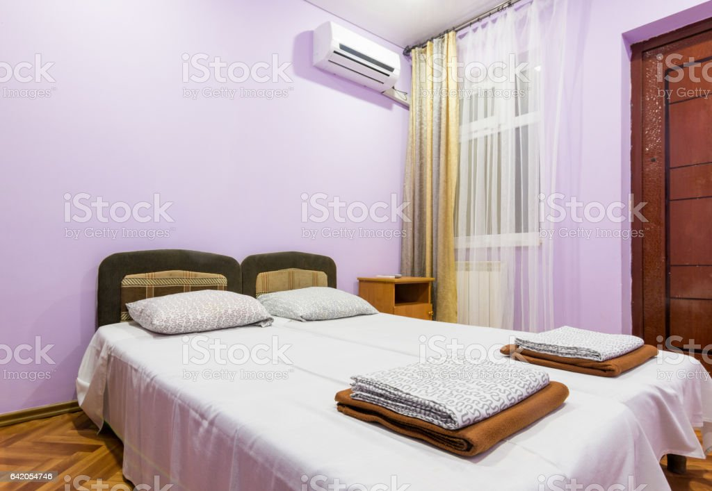 The interior of a small room with a double bed, a window and splitsistema stock photo