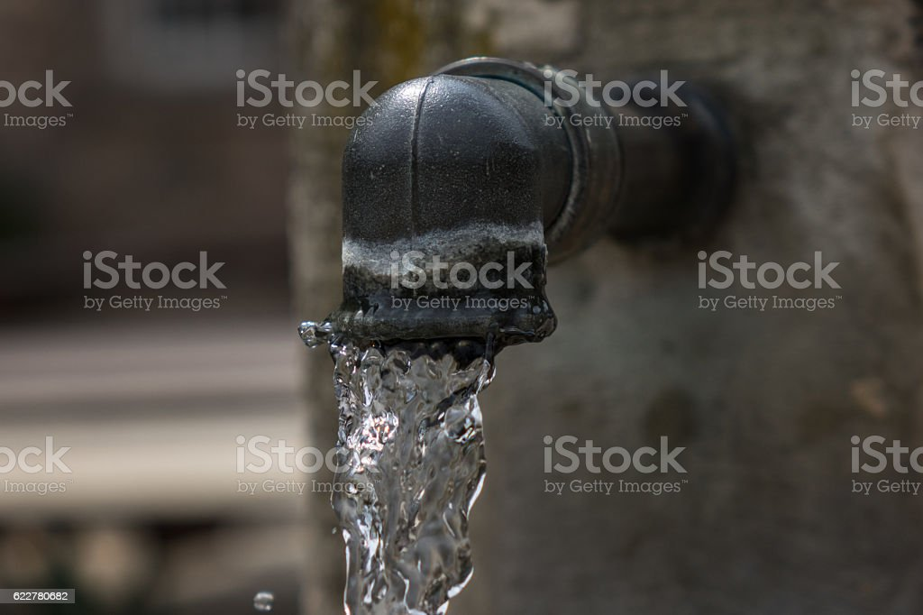The jet of drinking water from the spring crane stock photo