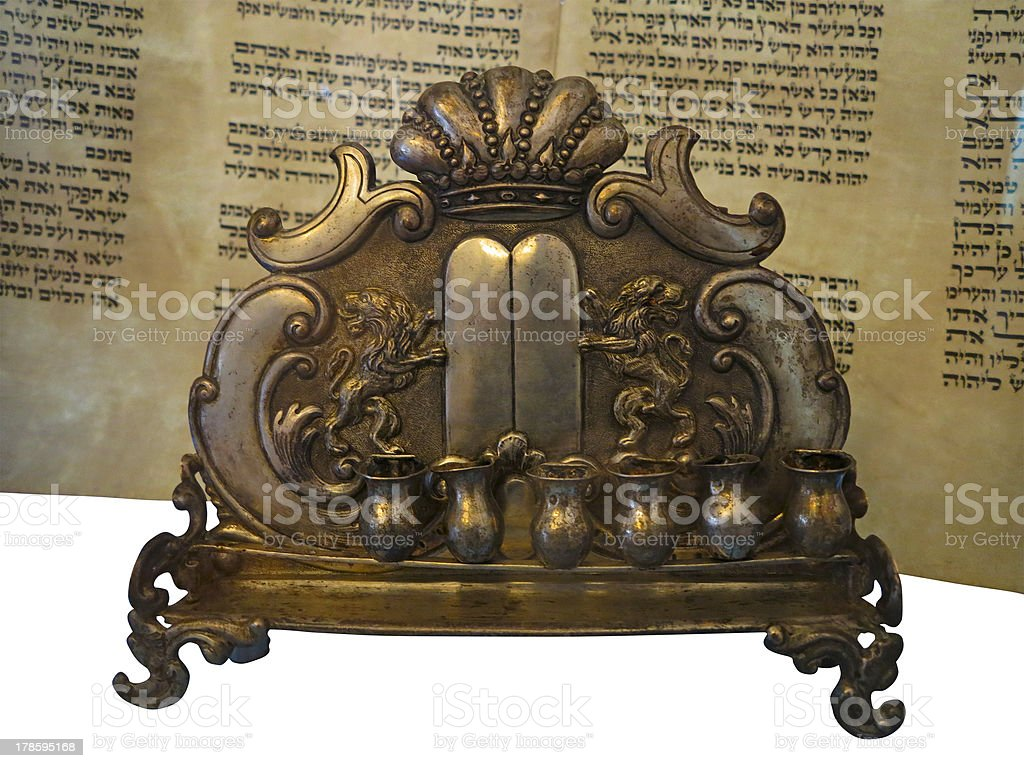 The Jewish Torah scroll and a gold menorah candle support royalty-free stock photo
