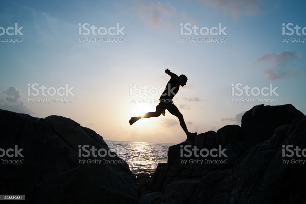 The jumping man on rocks stock photo